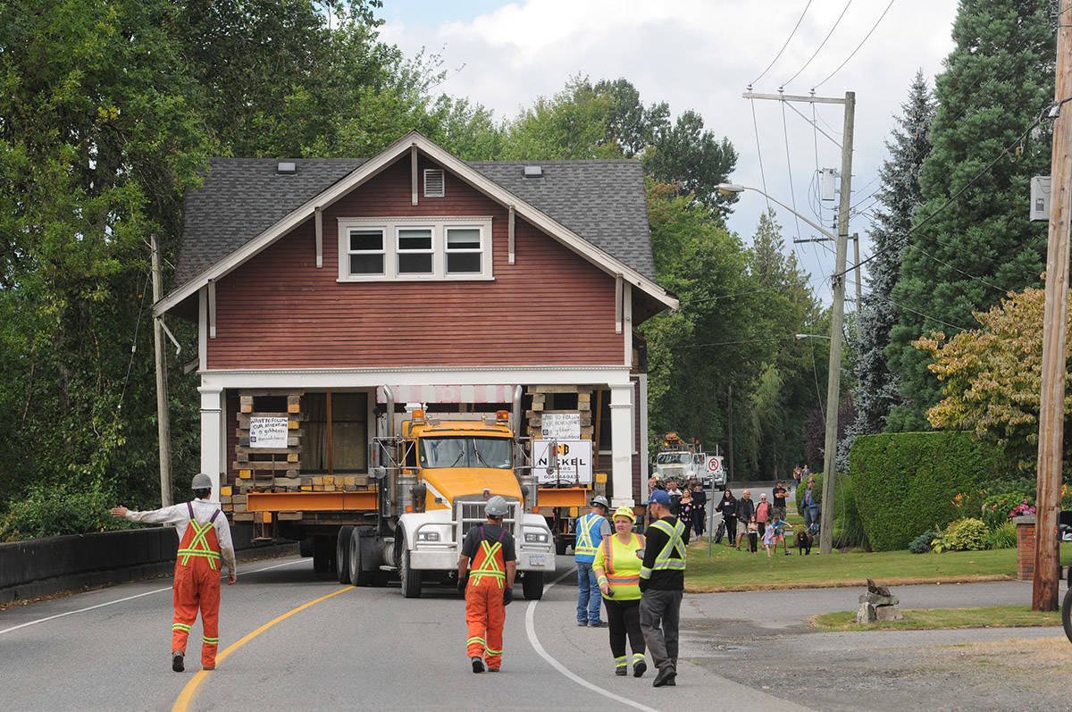 Crews with Nickel Bros move a 110-year-old heritage house along Hope River Road in Chilliwack on Friday, Aug. 7, 2020. The house was being relocated from 46239 Hope River Rd. to Riverside Drive that morning. (Jenna Hauck/ Chilliwack Progress)
