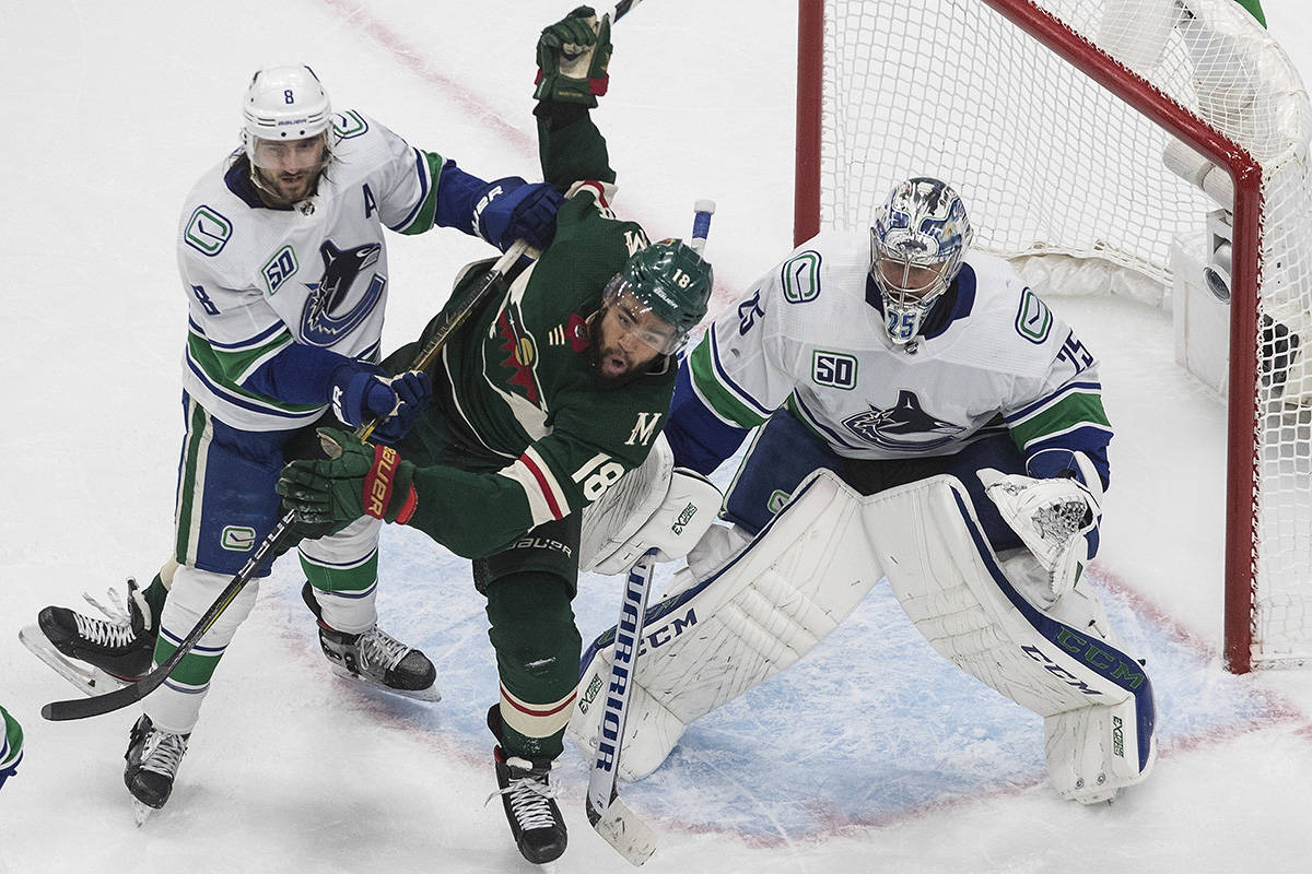 Minnesota Wild's Jordan Greenway (18) is pushed over by Vancouver Canucks' Christopher Tanev (8) as Canucks goalie Jacob Markstrom (25) looks for the shot during second period NHL qualifying round game action in Edmonton, on Friday August 7, 2020. THE CANADIAN PRESS/Jason Franson