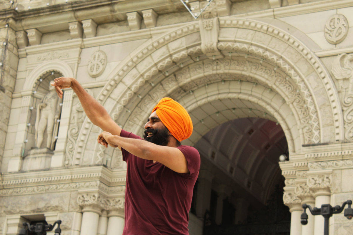 Gurdeep Pandher, a Yukon-based bhangra dancer, shows his skill with sweeping arm movements and high kicks on the steps of the BC Legislature Building on Saturday, Aug. 8, 2020. (Devon Bidal/News Staff)