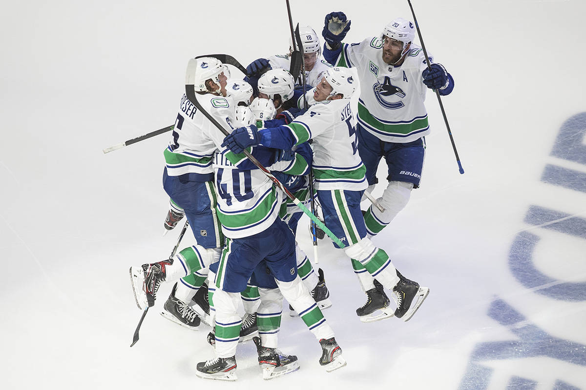 Vancouver Canucks players celebrate the win over the Minnesota Wild during overtime NHL qualifying round game action in Edmonton, on Friday August 7, 2020. The Canucks will take on the St. Louis Blues in first-round playoff action. THE CANADIAN PRESS/Jason Franson