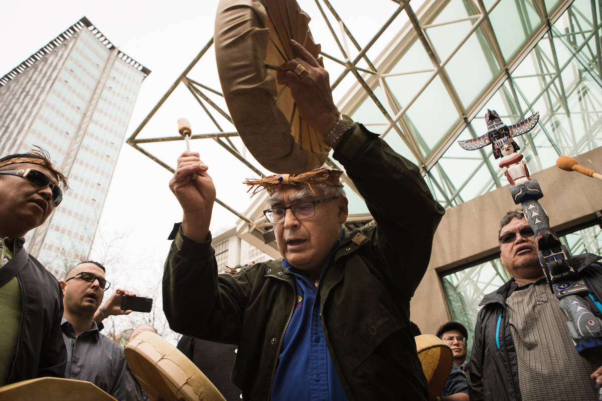 In a picture from April 2018, Wickaninnish (Clifford Atleo) plays the drum while singing the Nuu-chah-nulth song on the court steps in Vancouver after winning aboriginal fishing rights . Photo credit, Melody Charlie.