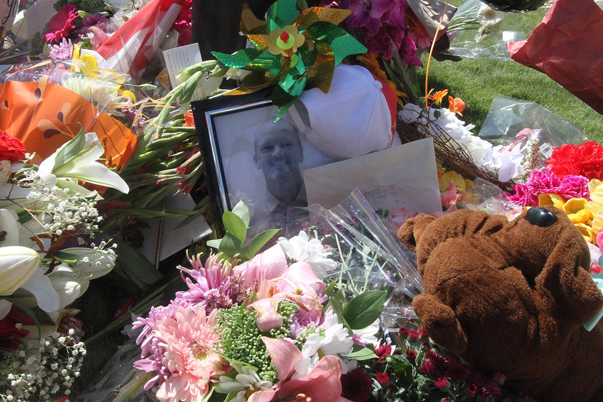 Dozens of bouquets of flowers, stuffed animals and other messages of gratitude and condolence have been left outside the walk-in clinic where Dr. Walter Reynolds was murdered on Monday. Photo by PAUL COWLEY/Advocate staff