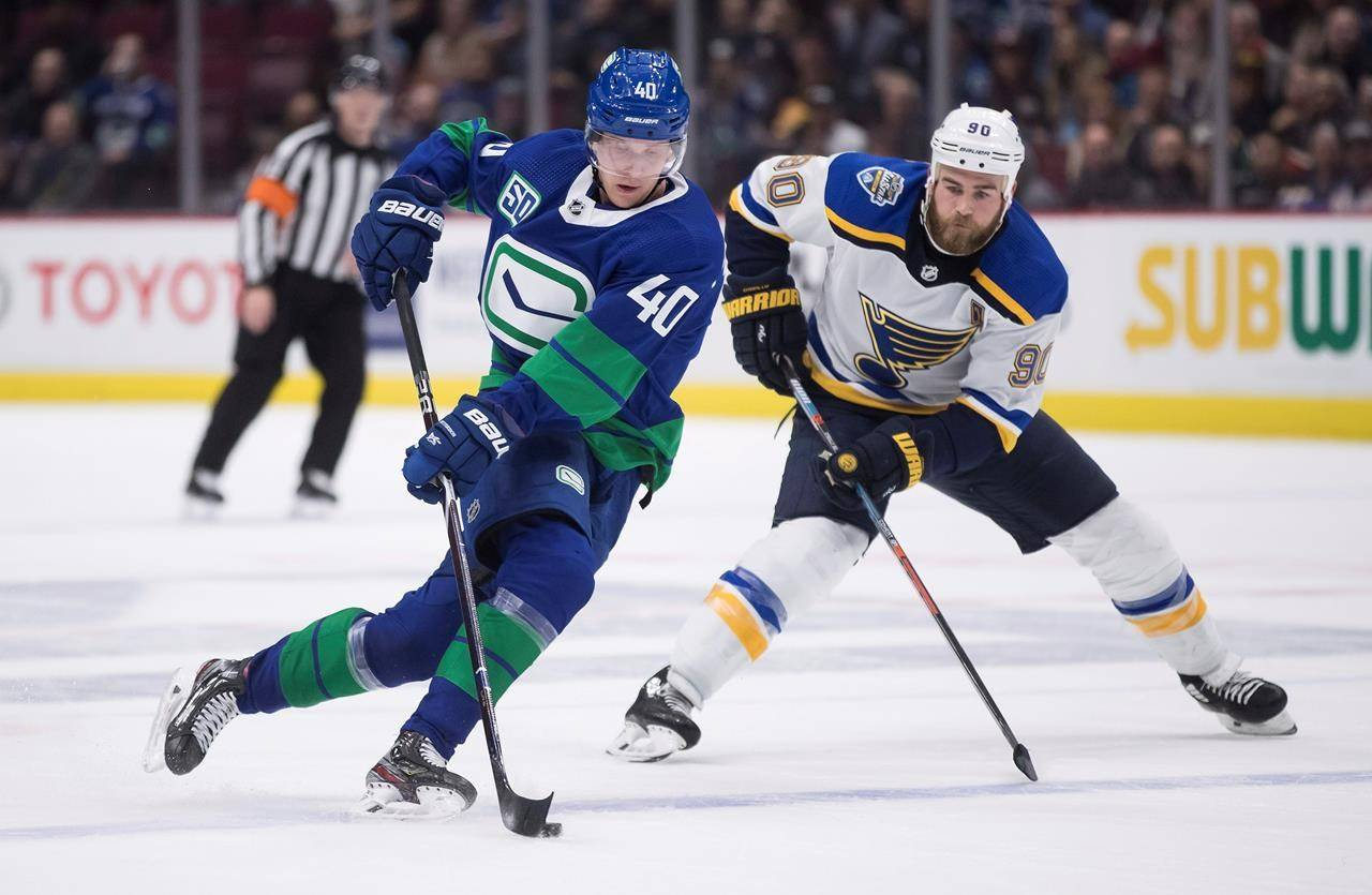 FILE - In this Nov., 5, 2019, file photo, Vancouver Canucks' Elias Pettersson (40), of Sweden, skates with the puck while being watched by St. Louis Blues' Ryan O'Reilly (90) during the second period of an NHL hockey game in Vancouver, British Columbia. If there's a polar opposite to the St. Louis Blues in terms of makeup and style, they'll face it in the Vancouver Canucks. (Darryl Dyck/The Canadian Press via AP, File)