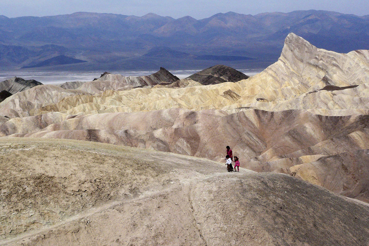 FILE - In this April 11, 2010, file photo, tourists walk along a ridge at Death Valley National Park, Calif. (AP Photo/Brian Melley, File)