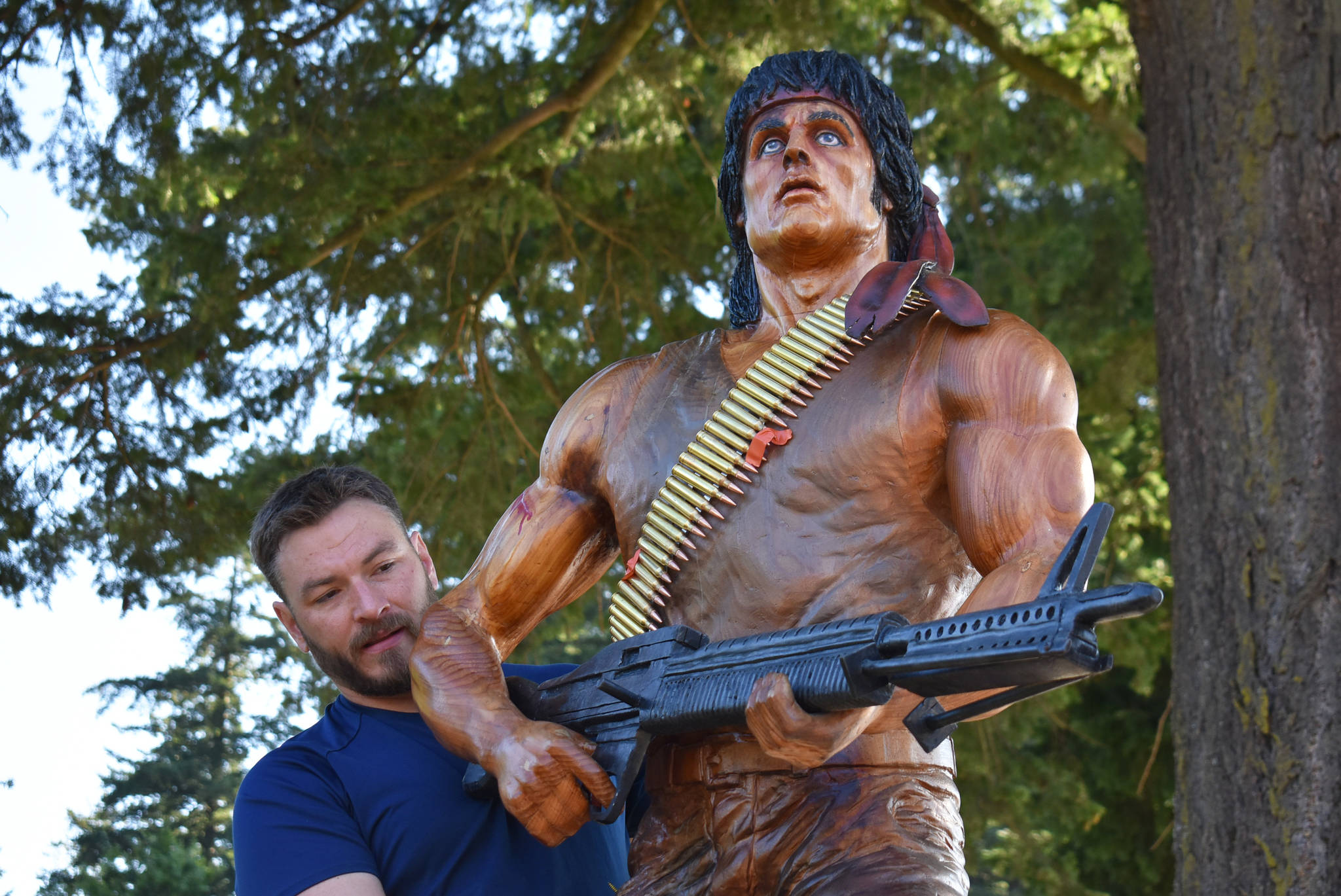 Carver Ryan Villiers puts finishing touches on the lifelike chainsaw carving of John J. Rambo (played by Sylvester Stallone) before it was installed at Hope's Memorial Park Aug. 14, 2020. (Emelie Peacock/Hope Standard)