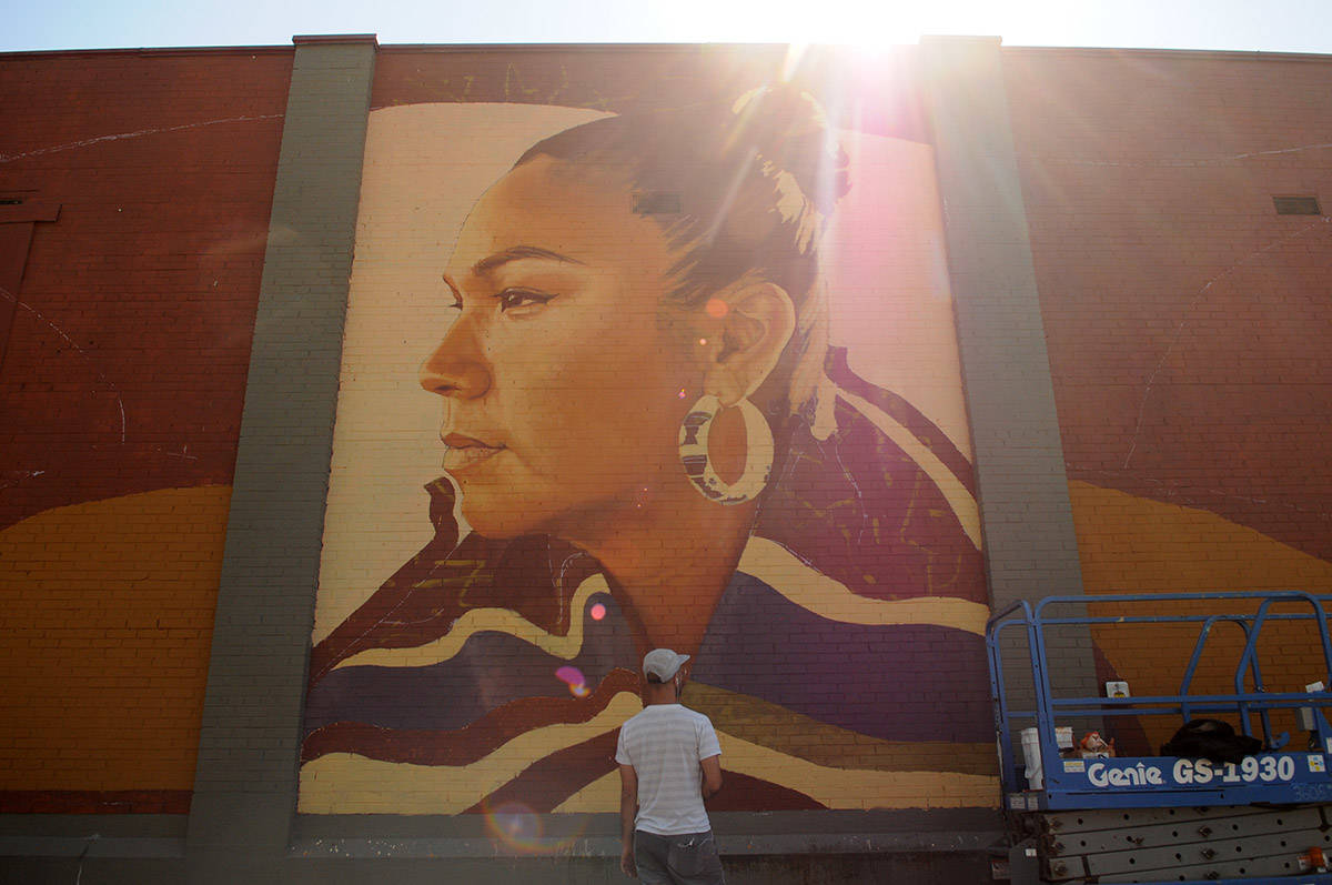 Artist Kevin Ledo steps back to look at his mural of Inez Louis while painting it on the back of a building on Victoria Avenue in downtown Chilliwack on Saturday, Aug. 15, 2020. (Jenna Hauck/ Chilliwack Progress)