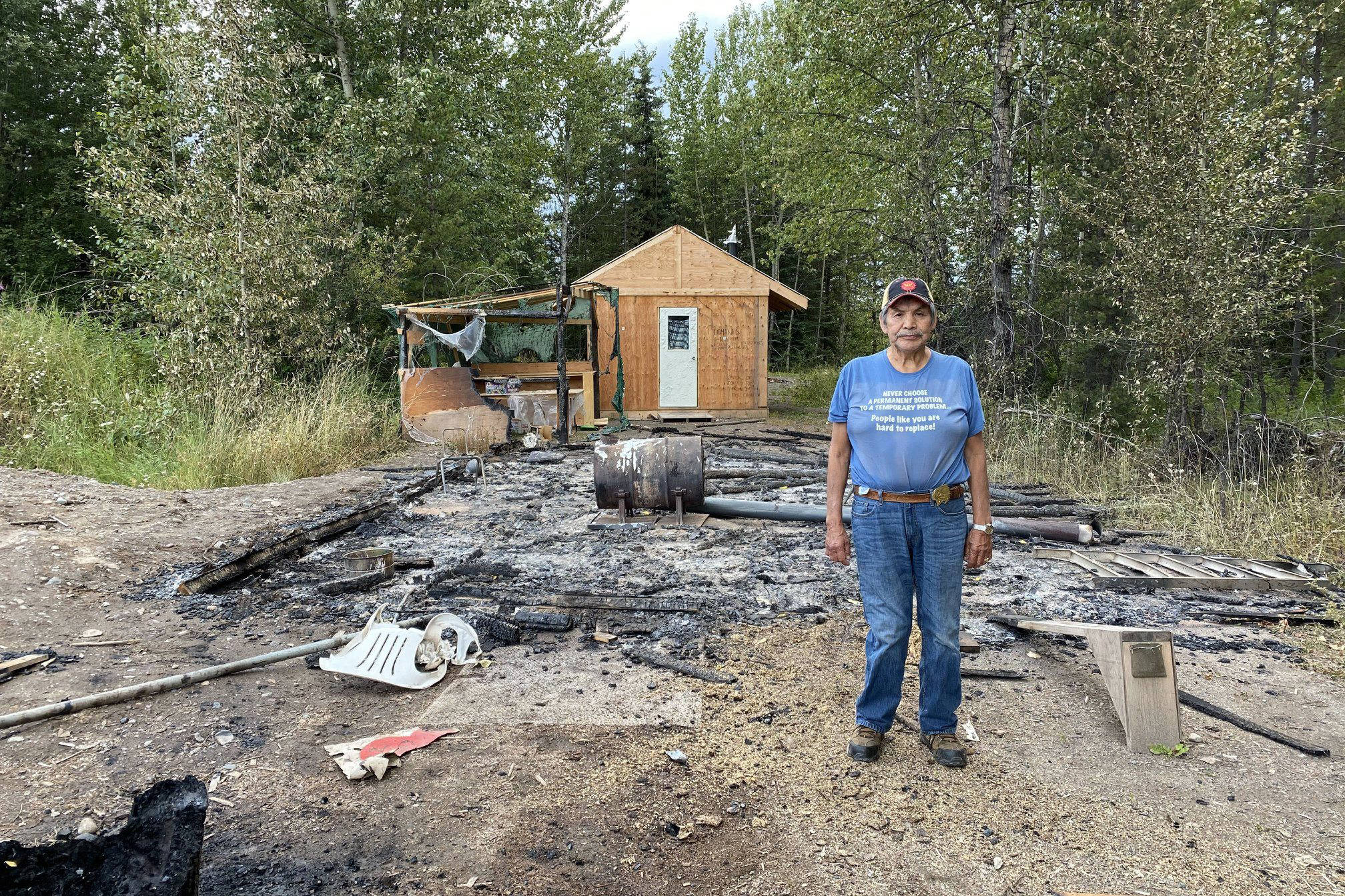 Chief Gisday'wa with the remains of a structure alongside the Morice Forest Service Road burned in an arson fire overnight from Aug. 14 to Aug. 15. Two suspects have now been identified. (Gidimt'en Clan photo)