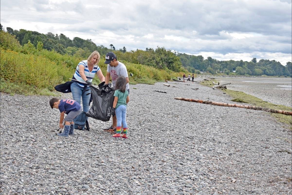 Alison and Masa Ito and their children Emi, 6, and Kai, 4, participate in a cleanup of East Beach Thursday (Aug. 20) morning. (Tracy Holmes photo)