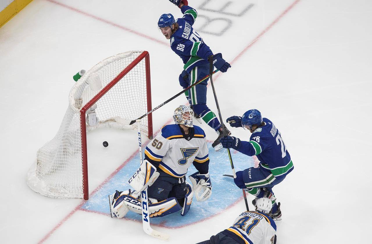 Vancouver Canucks' Antoine Roussel (26) and Adam Gaudette (88), celebrate a goal on St. Louis Blues goalie Jordan Binnington (50) during second period NHL Western Conference Stanley Cup playoff action in Edmonton on Friday, Aug. 21, 2020. THE CANADIAN PRESS/Jason Franson