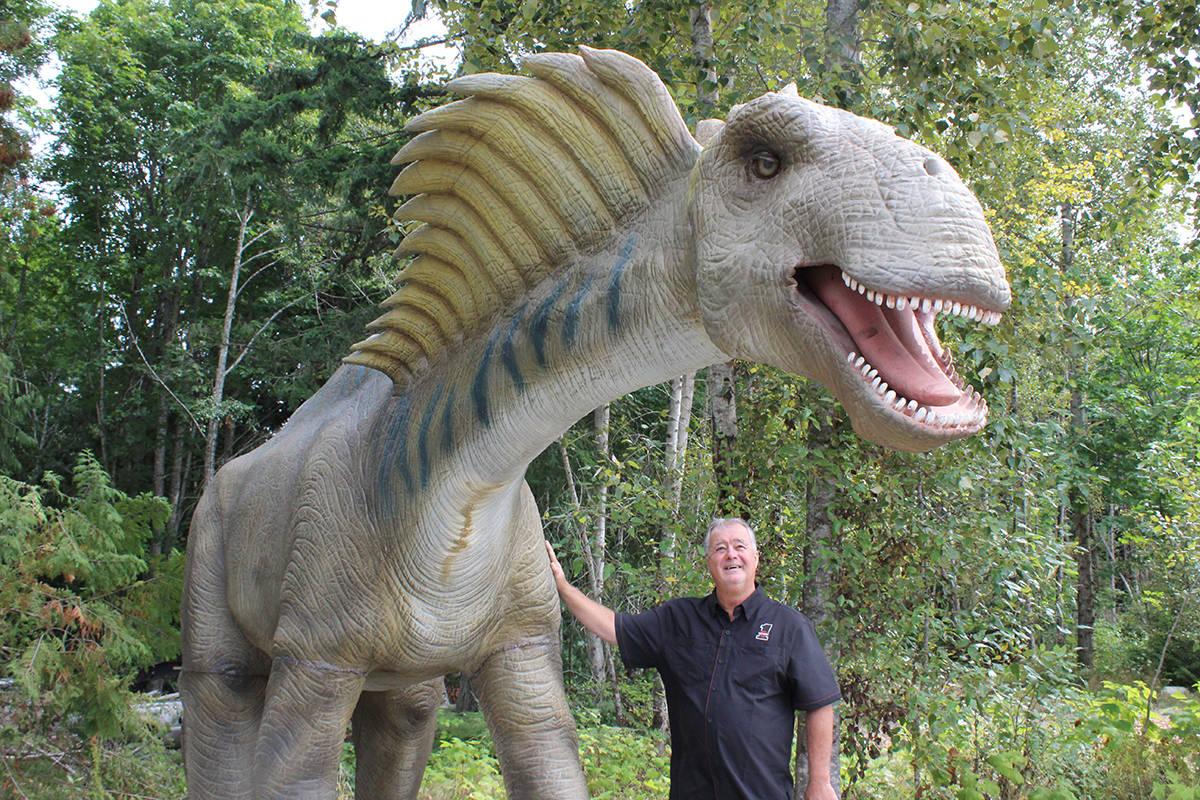 Stan Pottie with his new animatronic dinosaur named Lance on his property on Clark Drive West in Lantzville. (Greg Sakaki/News Bulletin)