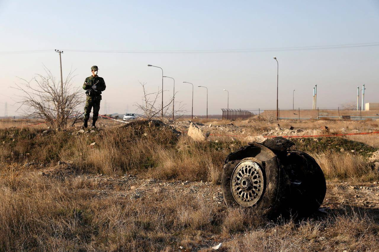 A police officer stands guard as debris is seen from an Ukrainian plane which crashed in Shahedshahr, southwest of the capital Tehran, Iran, January 8, 2020. Two federal cabinet ministers say they expect more answers from Iranian officials about an air strike that downed a passenger plane earlier this year, killing everyone on board. THE CANADIAN PRESS/AP, Ebrahim Noroozi