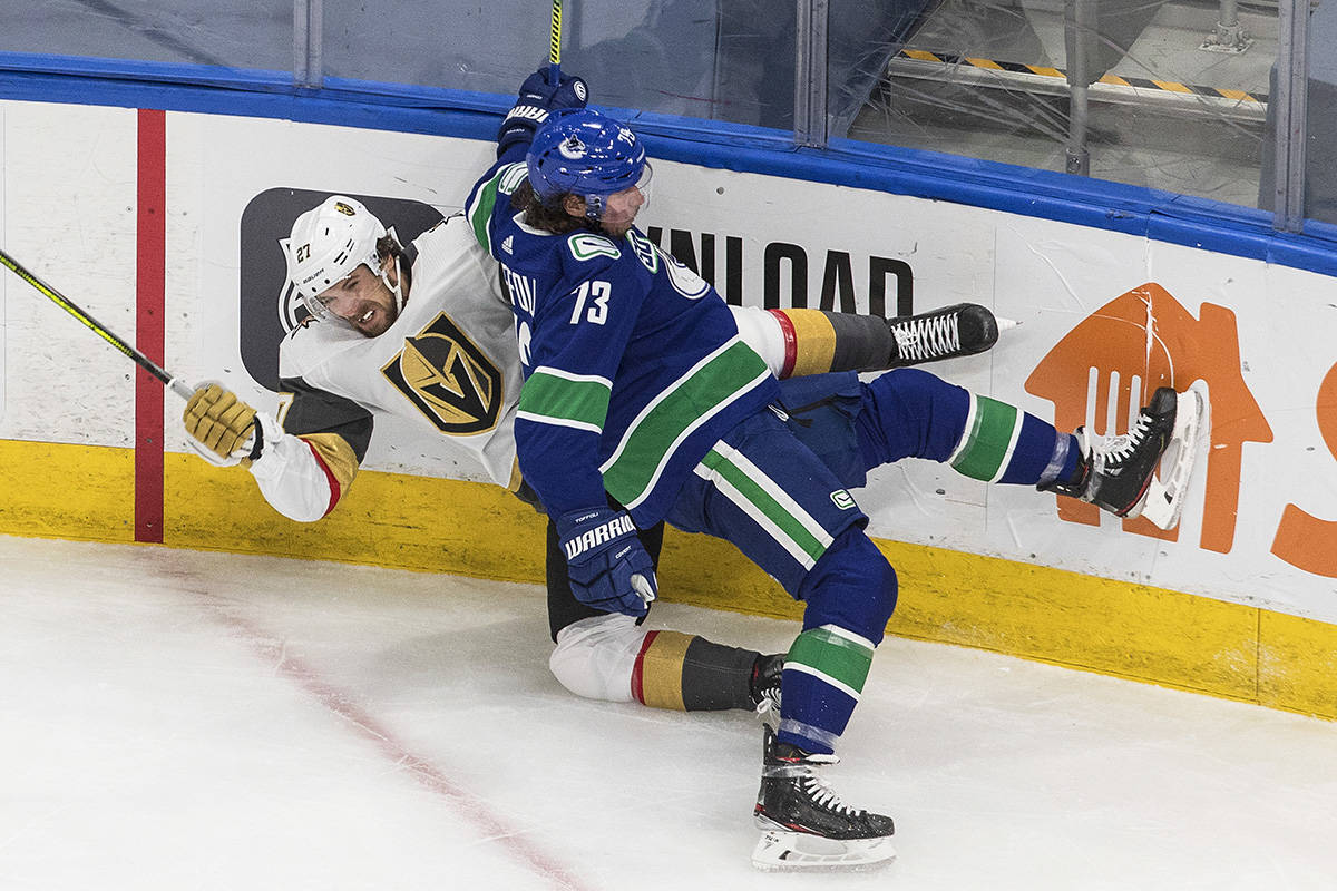 Vegas Golden Knights' Shea Theodore (27) is checked by Vancouver Canucks' Tyler Toffoli (73) during second period NHL Western Conference Stanley Cup playoff action in Edmonton on Saturday, Aug. 29, 2020. THE CANADIAN PRESS/Jason Franson