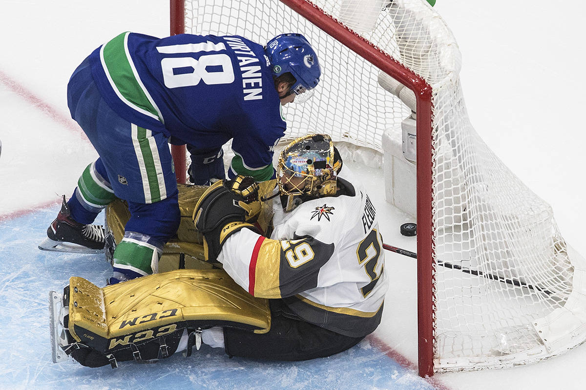 Vancouver Canucks' Jake Virtanen (18) falls on Vegas Golden Knights' goalie Marc-Andre Fleury (29) as the puck goes in the net during second period NHL Western Conference Stanley Cup playoff action in Edmonton on Sunday, Aug. 30, 2020. THE CANADIAN PRESS/Jason Franson