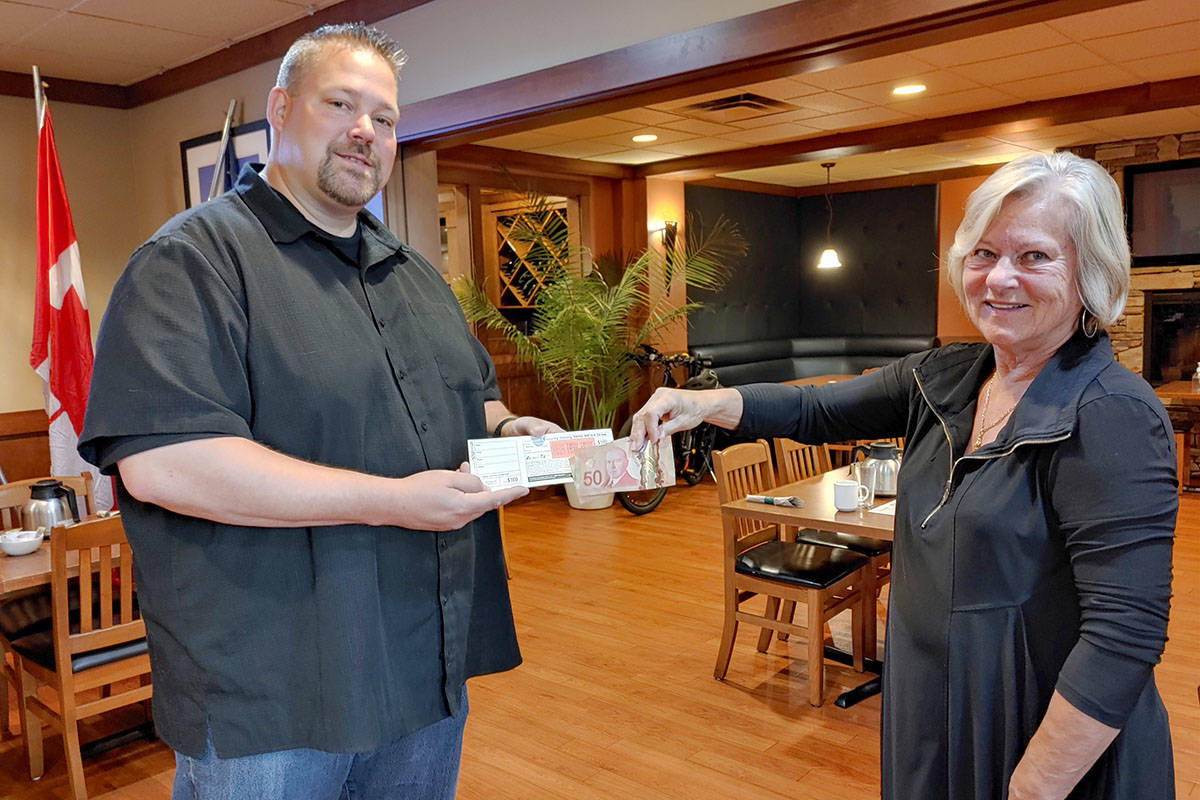 Celebrating Day One of the Langley Rotary 50/50 Mega Draw $200,000 Lottery campaign, Aldergrove Rotary Club member, Jason Froese, purchases tickets from club colleague Angie McDougall. Froese and all other ticket holders, have a chance to win up to $100,000. (Pauline Buck/Special to the Langley Advance Times)
