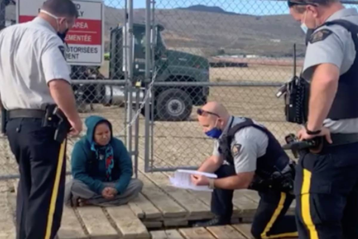 Kamloops Mounties speak with Lorelei Dick after she chained herself to a fence at a Trans Mountain pipeline expansion construction site at Kamloops Airport on Sept. 3. Photograph By MIRANDA DICK/FACEBOOK