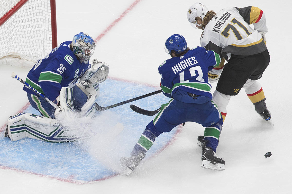 Vancouver Canucks goalie Thatcher Demko (35) makes the save as Vegas Golden Knights' William Karlsson (71) and Canucks' Quinn Hughes (43) battle for the rebound during second period NHL Western Conference Stanley Cup playoff action in Edmonton on Thursday, Sept. 3, 2020. THE CANADIAN PRESS/Jason Franson