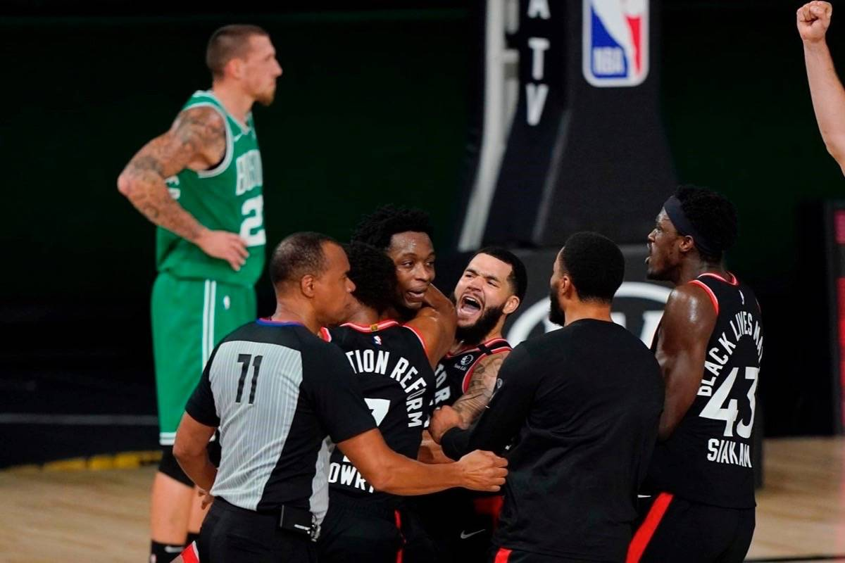 Teammates mob Toronto Raptors' OG Anunoby, second player from left, after Anunoby's game winning shot at the buzzer in the second half of an NBA conference semifinal playoff basketball game against the Boston Celtics Thursday, Sept 3, 2020, in Lake Buena Vista Fla. Celtic's Daniel Theis is at rear. THE CANADIAN PRESS/AP-Mark J. Terrill
