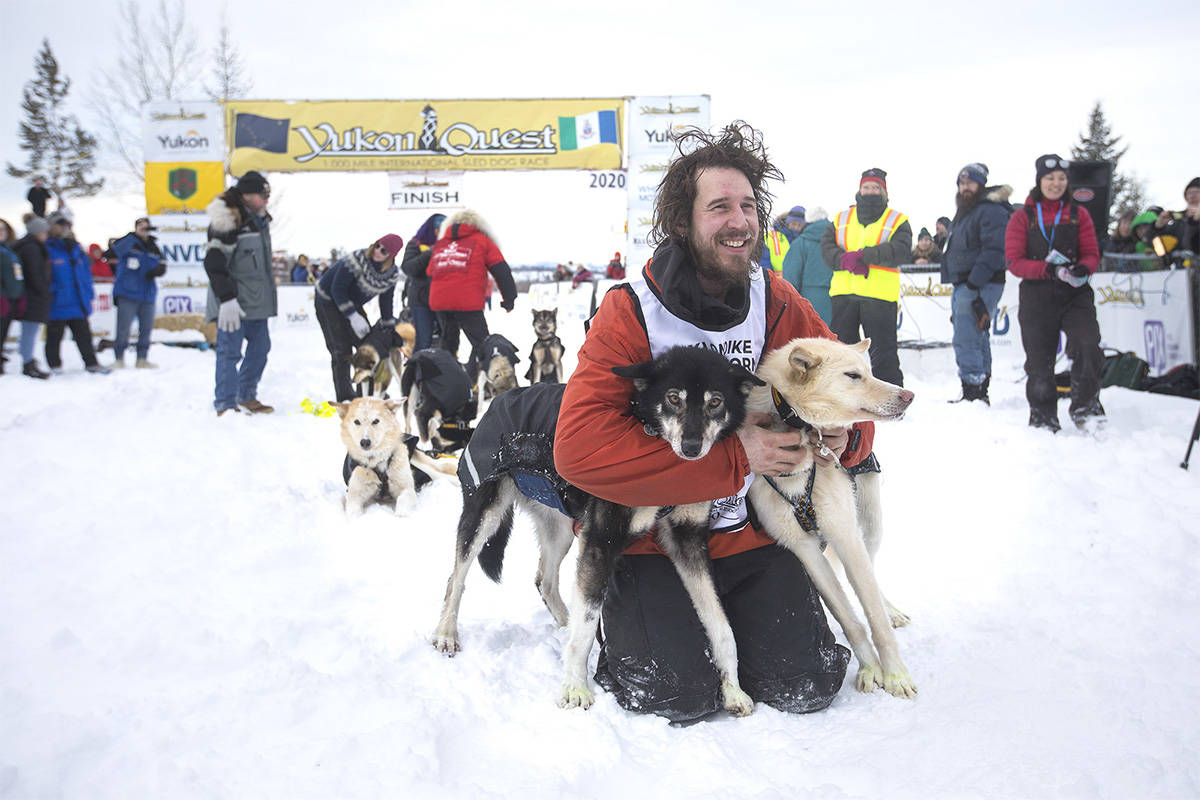Brent Sass poses with his lead dogs after crossing the finish line in Whitehorse on Feb. 11 to win his third Yukon Quest. (Crystal Schick/Yukon News file)