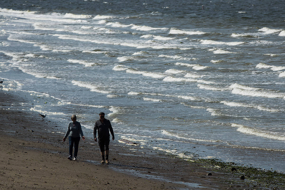 FILE — Strong winds whip up waves as a woman and man walk along the beach at English Bay in Vancouver, on Sunday May 5, 2019. THE CANADIAN PRESS/Darryl Dyck