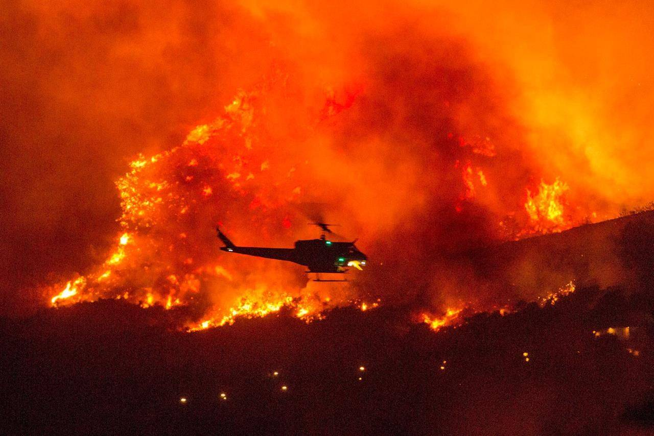 A helicopter prepares to drop water at a wildfire in Yucaipa, Calif., Saturday, Sept. 5, 2020. Three fast-spreading California wildfires sent people fleeing Saturday, with one trapping campers at a reservoir in the Sierra National Forest, as a brutal heat wave pushed temperatures into triple digits in many parts of state. (AP Photo/Ringo H.W. Chiu)