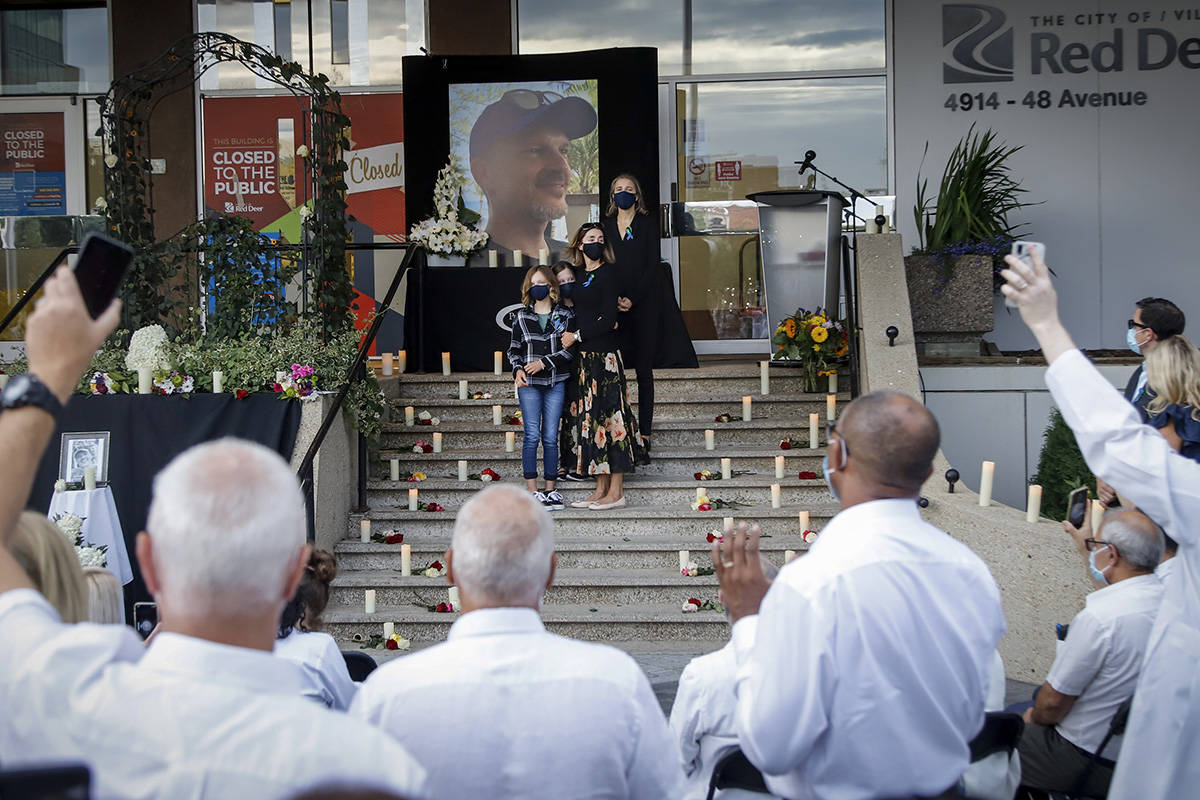 Healthcare workers and family members hold up phones as they attend a vigil for Dr. Walter Reynolds, a 45-year-old father of two, who was killed at a walk-in clinic earlier this week, in Red Deer, Alta., Friday, Aug. 14, 2020.THE CANADIAN PRESS/Jeff McIntosh