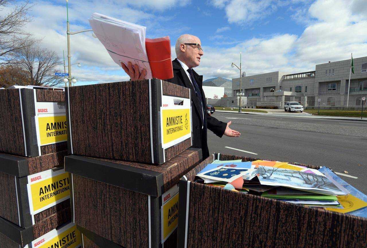 Alex Neve, Secretary General of Amnesty International Canada, holds up some of the 31,000 letters as they call on Saudi Arabia to free Raif Badawi as protesters take part in a rally outside the Embassy of Saudi Arabia in Ottawa on Monday, November 2, 2015. A prominent human rights organization says Canada is failing to bring suspected war criminals to justice. THE CANADIAN PRESS/Sean Kilpatrick