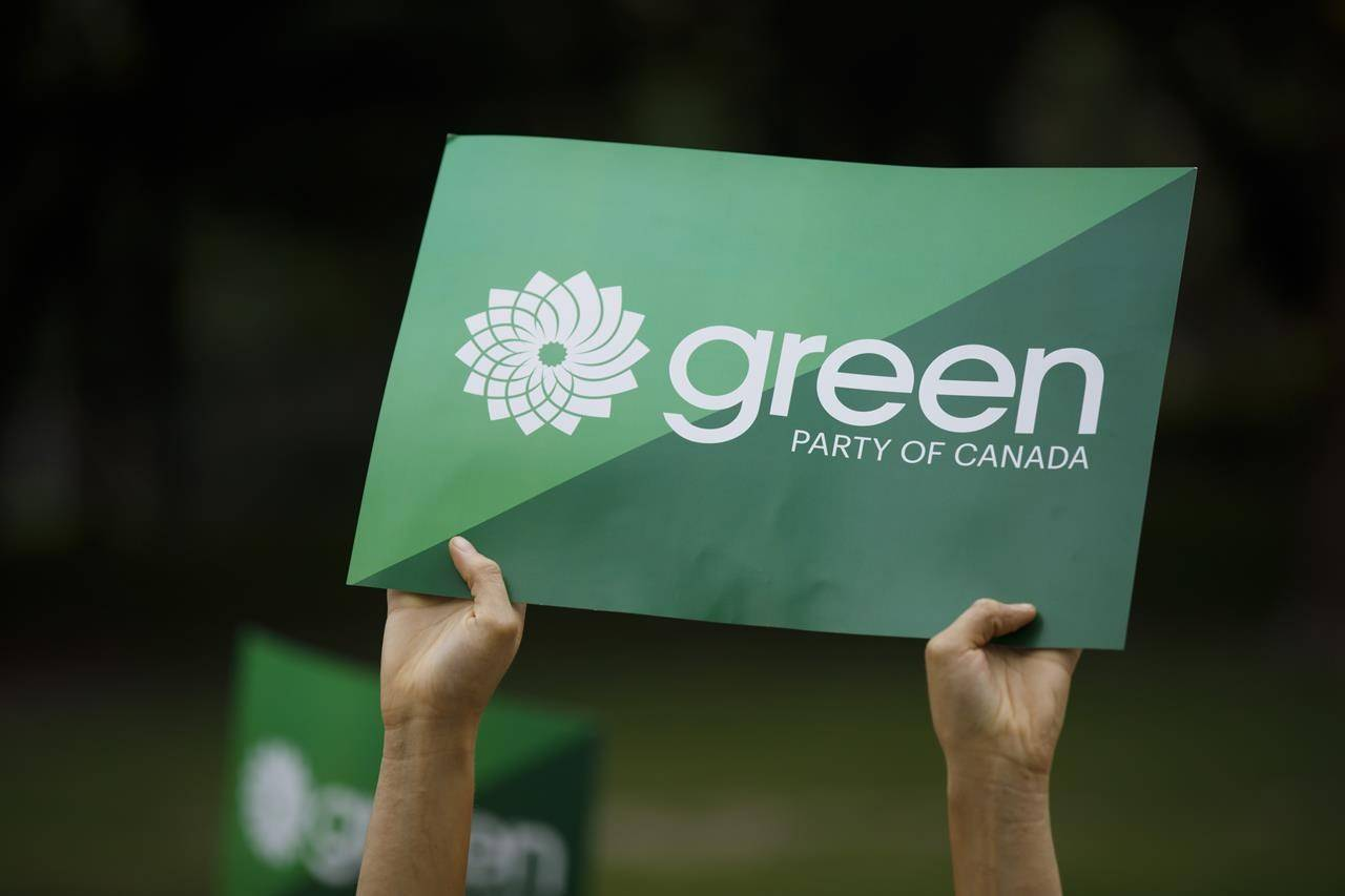 A supporter holds a sign for the Green Party of Canada in Toronto, Tuesday, Sept. 3, 2019. More than 35,000 people are eligible to cast a vote in next month's Green party leadership race. THE CANADIAN PRESS/Cole Burston