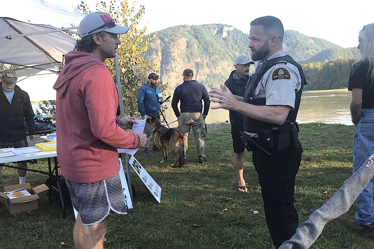 DFO fishery officer Mike Fraser chats with Valdy Widera of Surrey, at the bar-fishing demonstration fishery, Sept. 9, 2020, at Island 22 Regional Park in Chilliwack, explaining the event was not sanctioned by DFO. (Jennifer Feinberg/ Chilliwack Progress)