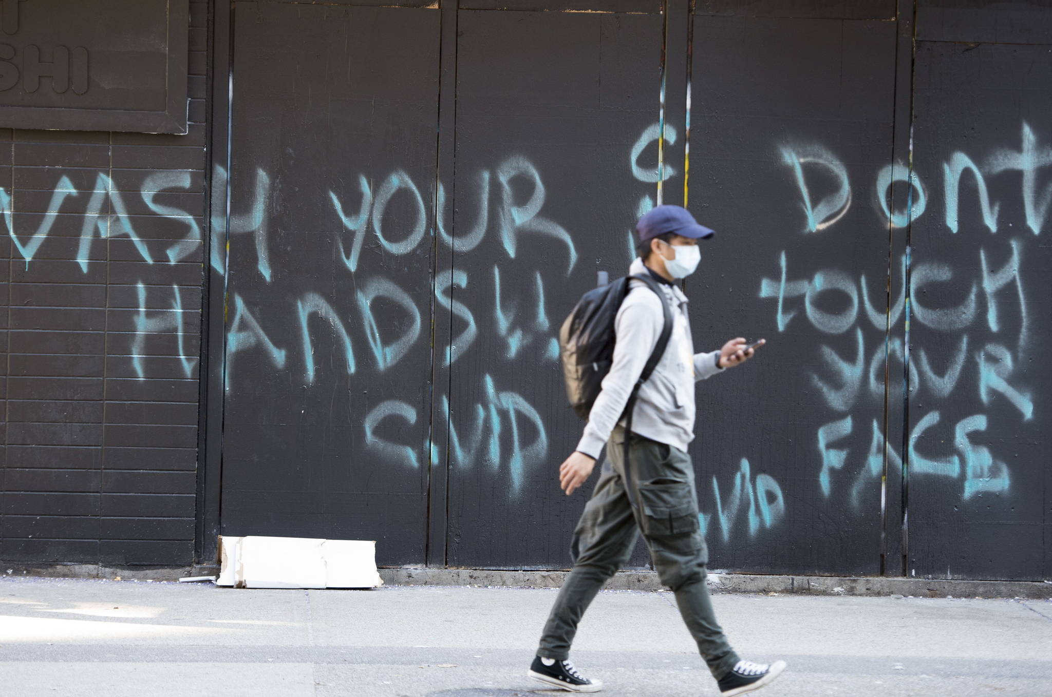 "A man wearing a protective face mask walks past a spray painted wall saying ""Wash your hands and don't touch your face"" in downtown Vancouver, Wednesday, March 18, 2020. THE CANADIAN PRESS/Jonathan Hayward"