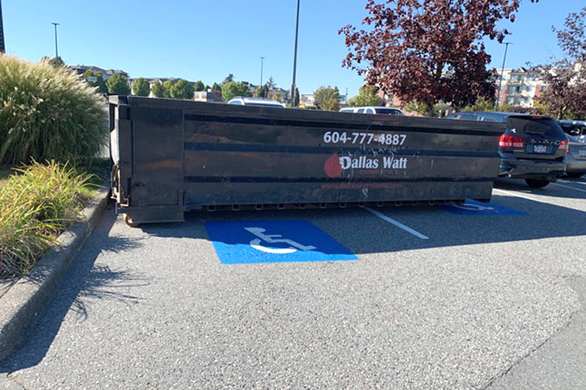 With few designated parking spots available for people with disabilities in the Langley Mall, this resident was surprised to see a huge dumpster parked in two of those spaces. (Geoff Straker/Special to Langley Advance Times)