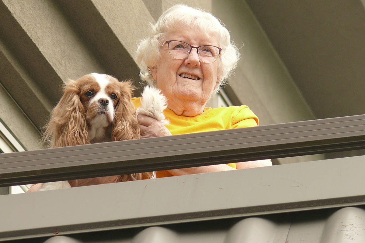 Eileen Bevis and her canine companion viewed the parade from a balcony at the Langley Chartwell Gardens retirement residence on Saturday, Sept. 12. (Dan Ferguson/Langley Advance Times)