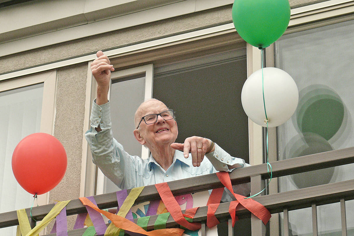 John Kromhoff gave a thumbs-up from his balcony at the Langley Chartwell Gardens retirement residence on Saturday, Sept. 12. (Dan Ferguson/Langley Advance Times)