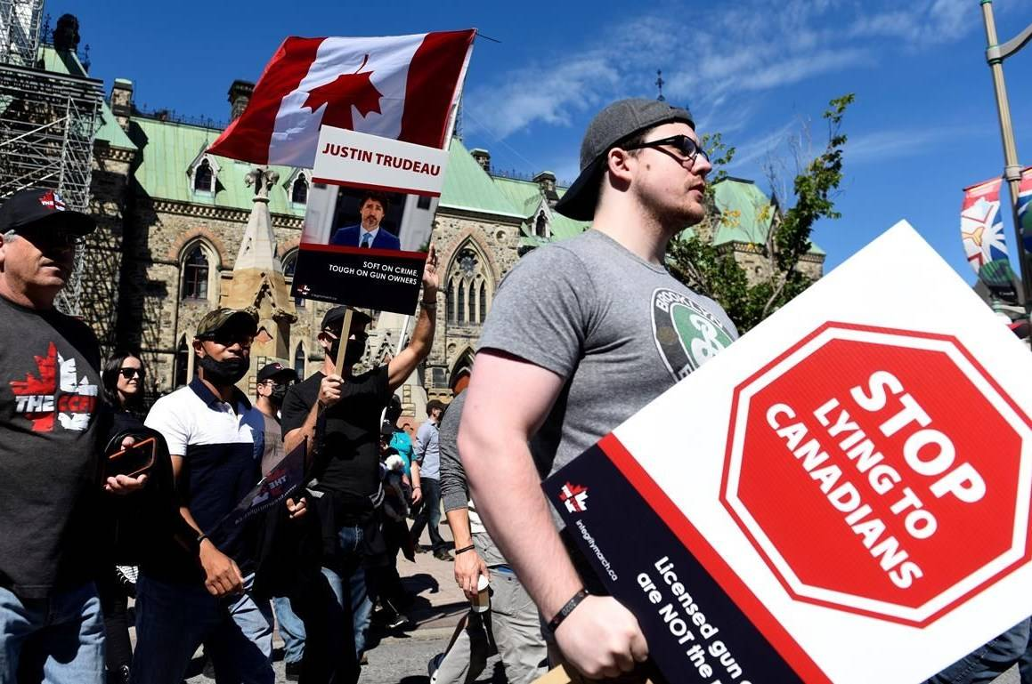 Gun owners hold signs criticizing Prime Minister Justin Trudeau as they participate in a rally organized by the Canadian Coalition for Firearm Rights against the government's new gun regulations, on Parliament Hill in Ottawa, on Saturday, Sept. 12, 2020. THE CANADIAN PRESS/Justin Tang