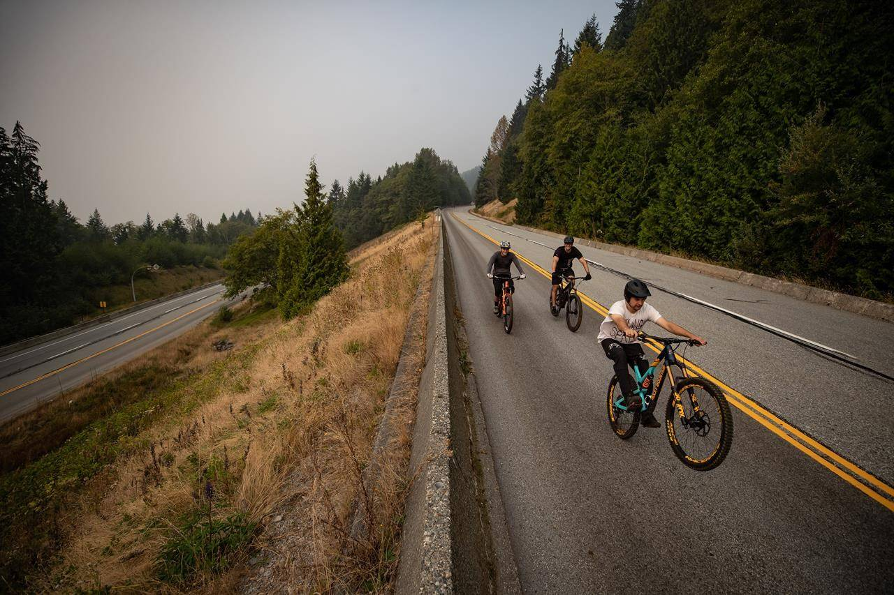 Smoke from wildfires burning in the U.S. fills the air as people ride bikes down the road at Cypress Provincial Park, in West Vancouver, B.C,, on Saturday, September 12, 2020. THE CANADIAN PRESS/Darryl Dyck