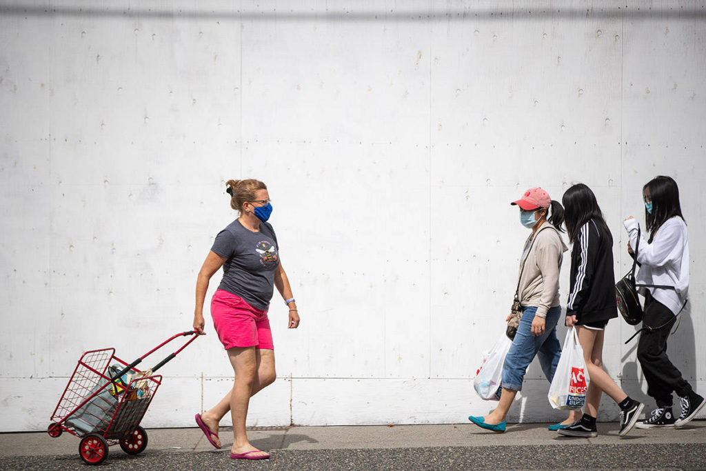 People wear face masks to curb the spread of COVID-19 while walking in Vancouver, B.C., Sunday, Aug. 30, 2020. THE CANADIAN PRESS/Darryl Dyck