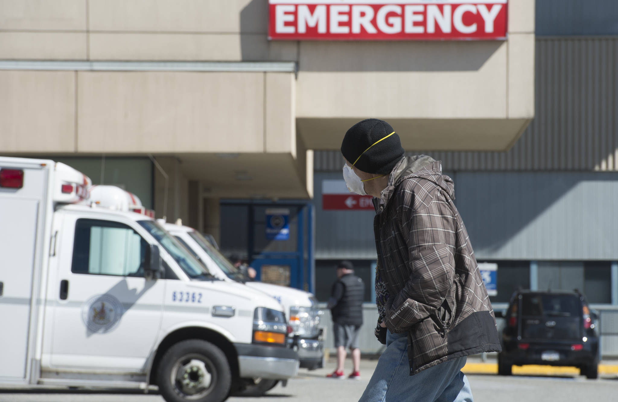 A man wears a protective face mask as he walks past the emergency department of the Royal Columbian Hospital in New Westminster, B.C. Friday, April 3, 2020. New data finds emergency department visits dropped by 25 per cent in the early days of the COVID-19 pandemic. THE CANADIAN PRESS/Jonathan Hayward