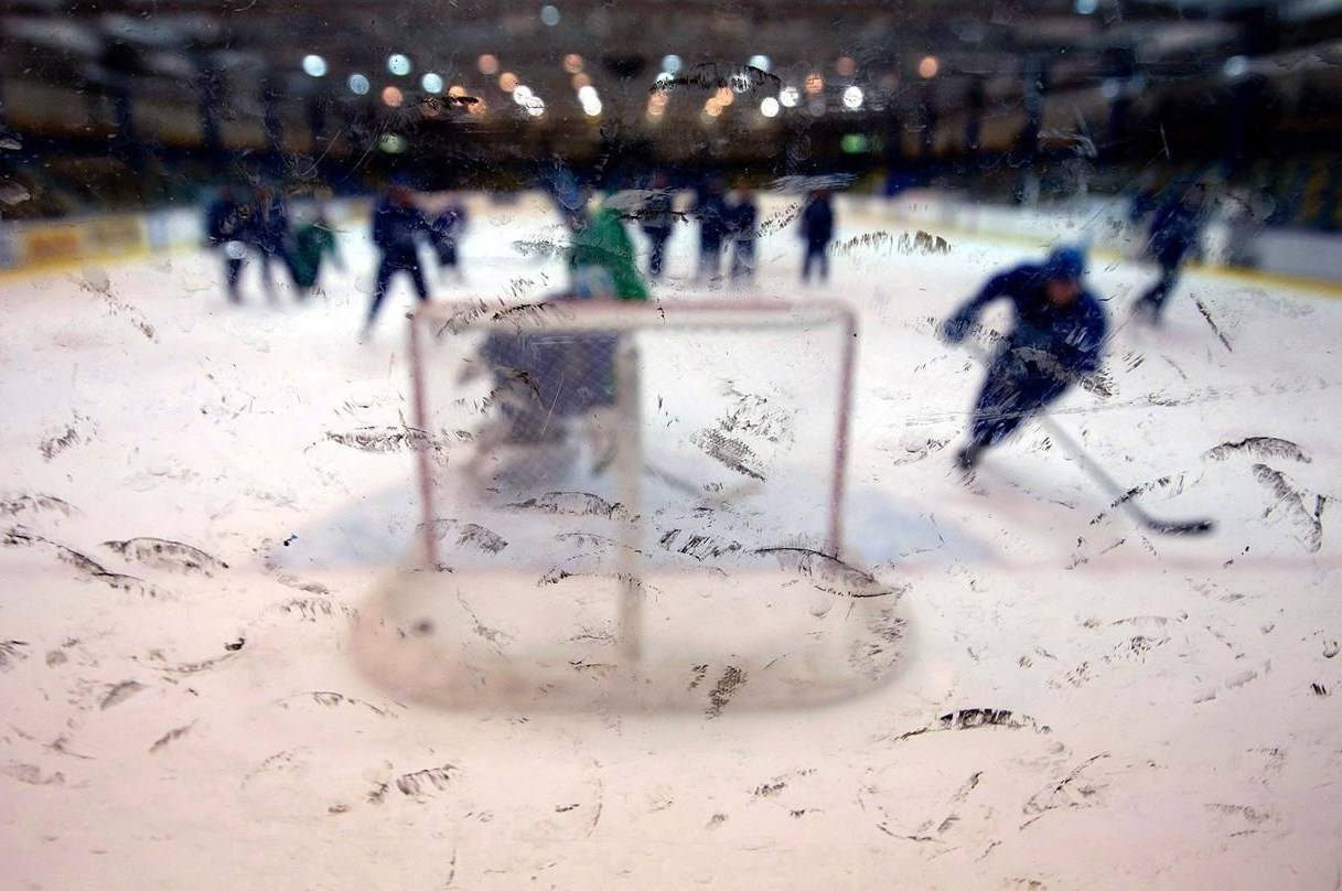 Rubber marks from pucks dot the glass as Vancouver Canucks players take part in an optional hockey practice attended by a small number of players in Vancouver, B.C., on Thursday June 2, 2011. A proposed $825 million class-action lawsuit alleges some of North America's most powerful hockey leagues are conspiring to limit opportunities for young players. THE CANADIAN PRESS/Darryl Dyck
