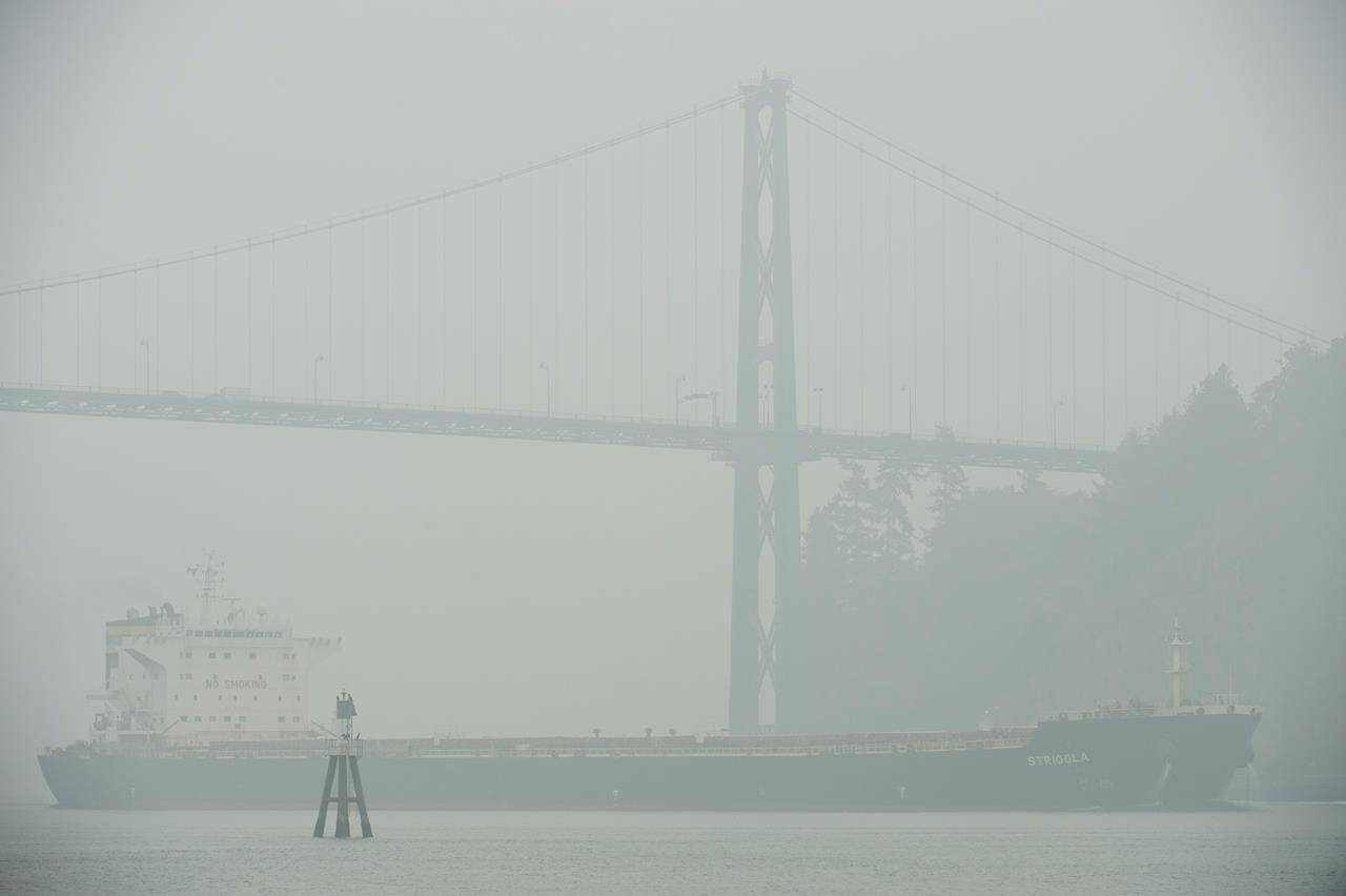 A ship comes through the smokey air as it goes under the Lion's Gate Bridge in Vancouver, B.C., Monday, Sept. 14, 2020. THE CANADIAN PRESS/Jonathan Hayward
