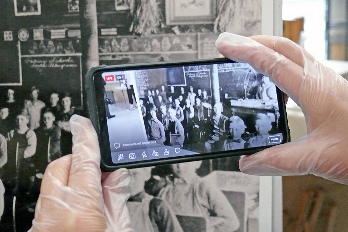 A gloved visitor focuses on a historical photograph at the Community Heritage Day exhibition held at the Aldergrove legion by the Alder Grove Heritage Society (AGHS) on Saturday, Sept. 19. (Dan Ferguson/Langley Advance Times)