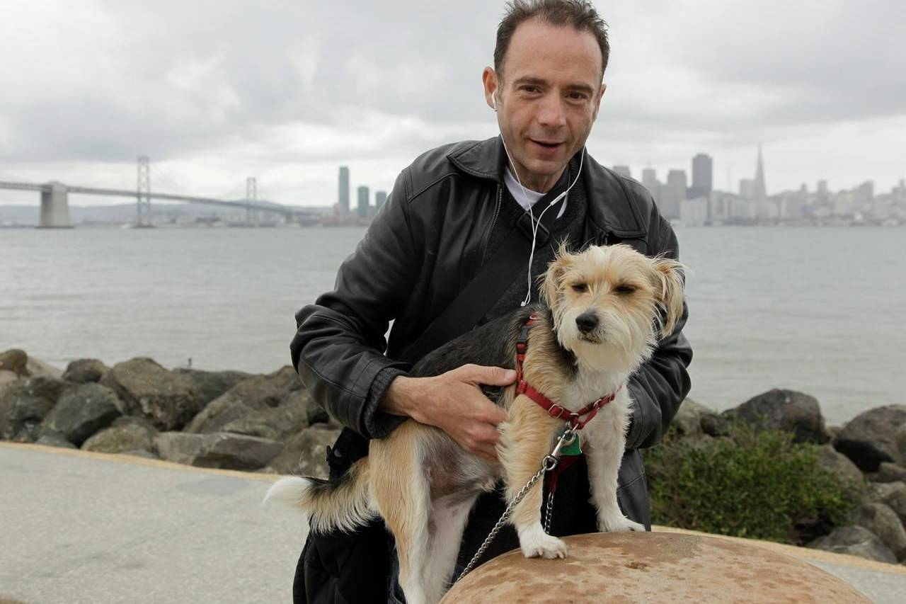 FILE - This May 16, 2011 photo shows Timothy Ray Brown with his dog, Jack, on Treasure Island in San Francisco. Brown, who was known for years as the Berlin patient, had a transplant in Germany from a donor with natural resistance to the AIDS virus. It was thought to have cured Brown's leukemia and HIV. But in an interview Thursday, Sept. 24, 2020, Brown said his cancer returned last year and has spread widely. His case has inspired scientists to seek more practical ways to try to cure the disease. (AP Photo/Eric Risberg)