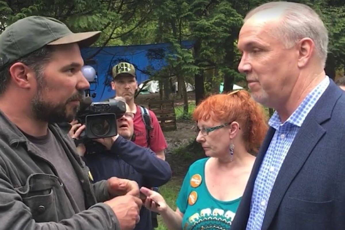 Tent camp organizer Ivan Drury demands housing from NDP leader John Horgan during his campaign stop in Maple Ridge, May 2017. He faced protests at his latest campaign appearance there over his government's imposition of transitional housing. (Maple Ridge News)