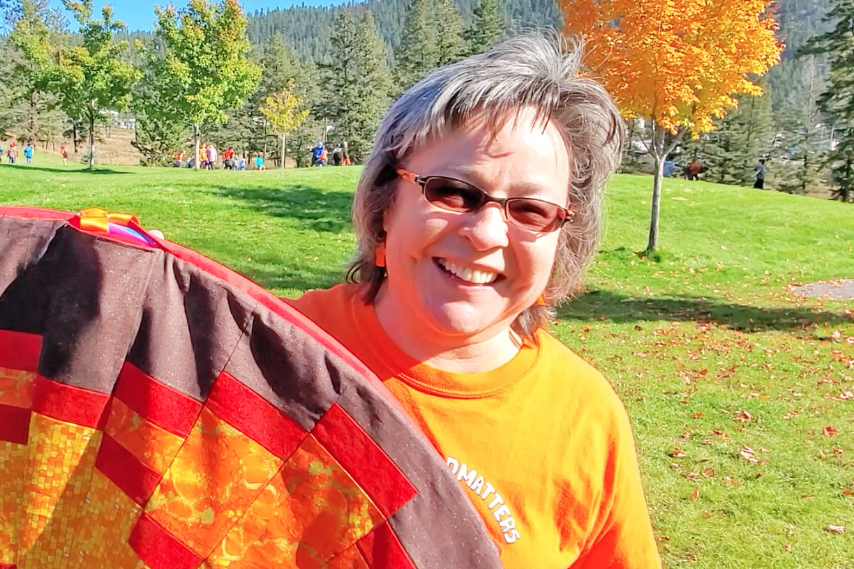 Phyllis Webstad holds up the gathering blanket the staff and students of Dog Creek school made and presented to her during Orange Shirt Day.