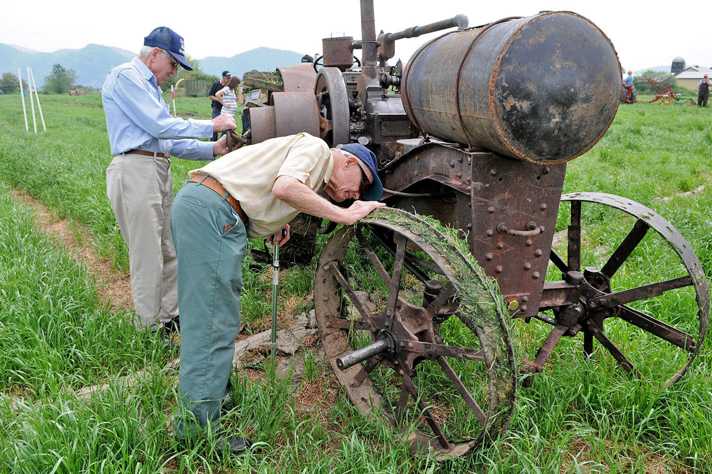 Monday, Oct. 12 is Old Farmers' Day. Pictured here are Aaron Warkentin (right) and Abe Goertz as they take a close look at a 1919 tractor during the 91st annual Chilliwack Plowing Match in Abbotsford on May 11, 2013. (Jenna Hauck/ Black Press file)