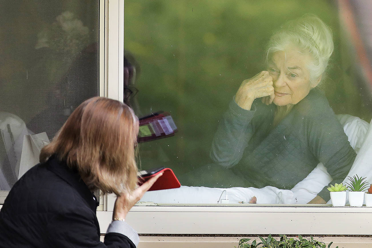 Judie Shape, right, who has tested positive for the new coronavirus, but isn't showing symptoms, smiles as she visits through the window and on the phone with her daughter Lori Spencer, left, Tuesday, March 17, 2020, at the Life Care Center in Kirkland, Wash., near Seattle. In-person visits are not allowed at the nursing home, which is at the center of the outbreak of the new coronavirus in the United States. (AP Photo/Ted S. Warren)