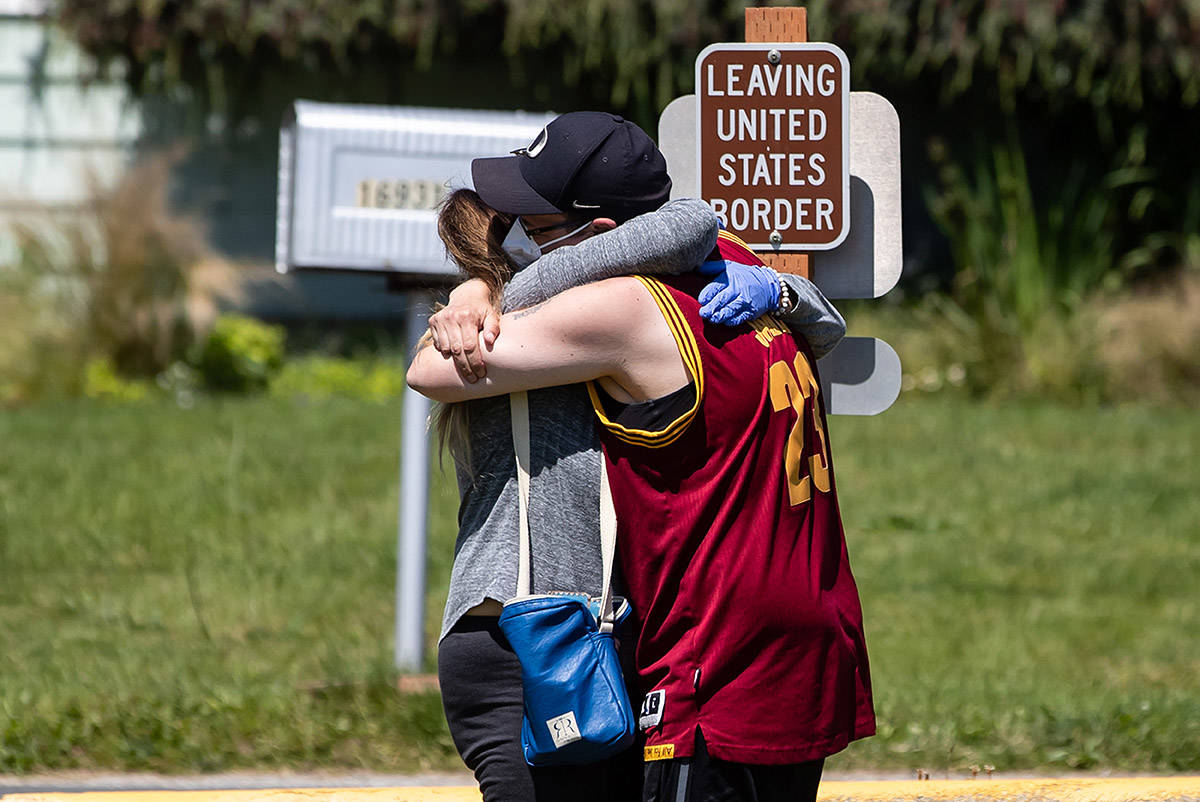 Desiree Osborne, right, of Bellingham, Wash., and her mother Judy Utgaard, of Port Coquitlam, B.C., embrace for the first time in five months, after Utgaard stepped across the Canada-United States border in Blaine, Wash., from Surrey, B.C., into Peace Arch Historical State Park, on Sunday, July 5, 2020. THE CANADIAN PRESS/Darryl Dyck