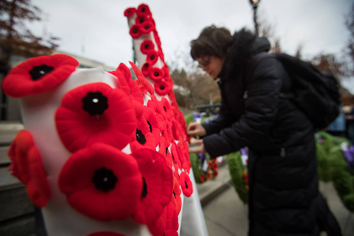 A woman pins her poppy on a cross after a Remembrance Day ceremony at the cenotaph in New Westminster, B.C., on Monday November 11, 2019. THE CANADIAN PRESS/Darryl Dyck
