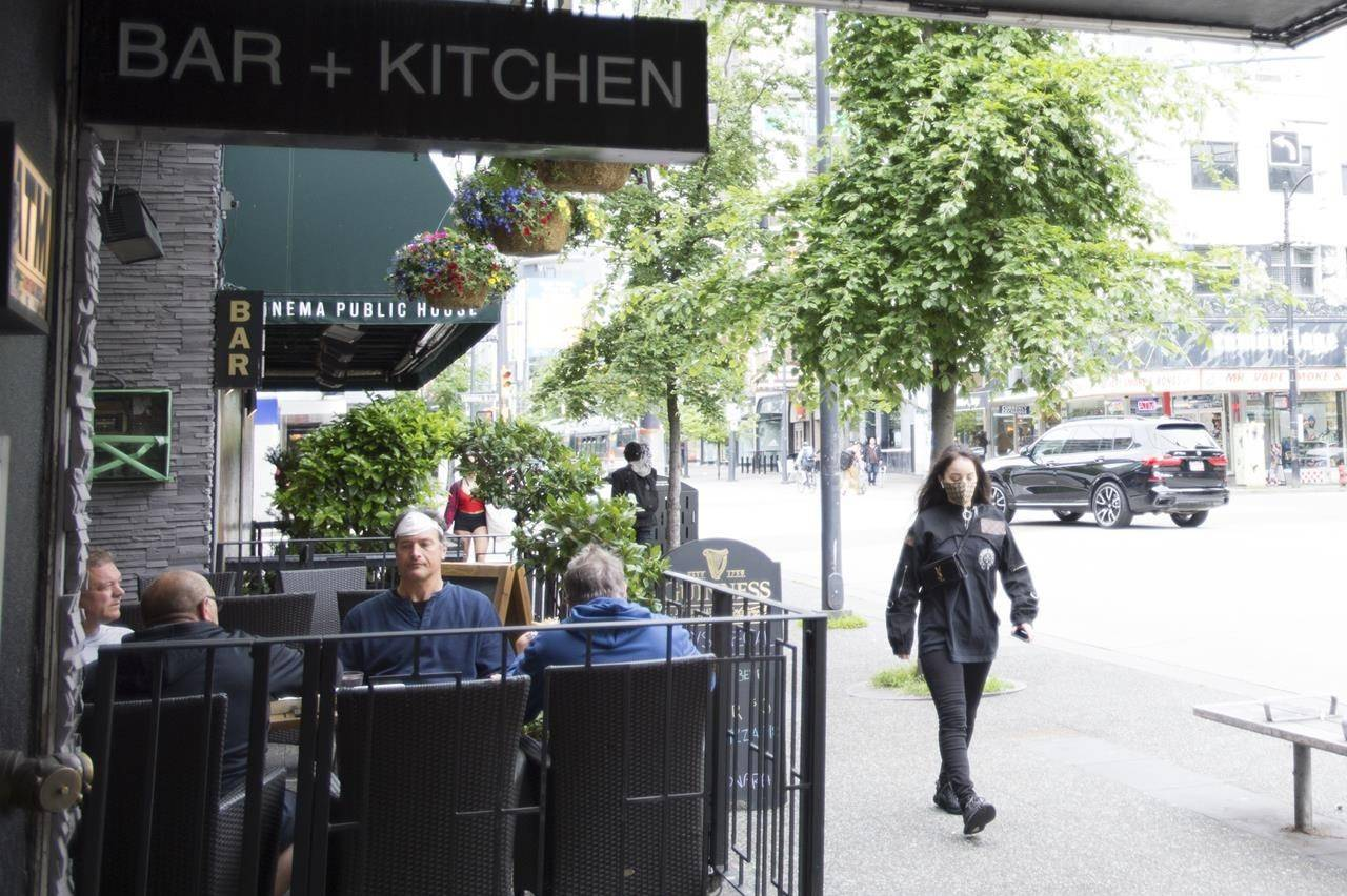 A woman wears a protective face mask as she walks past a opened restaurant patio on Granville Street in Vancouver, Wednesday, May 20, 2020. The pandemic may serve as an opportunity for the restaurant industry to innovate in order to avoid closures as public health measures limit the sale of booze and erode already thin profit margins, say addiction and business experts. THE CANADIAN PRESS/Jonathan Hayward