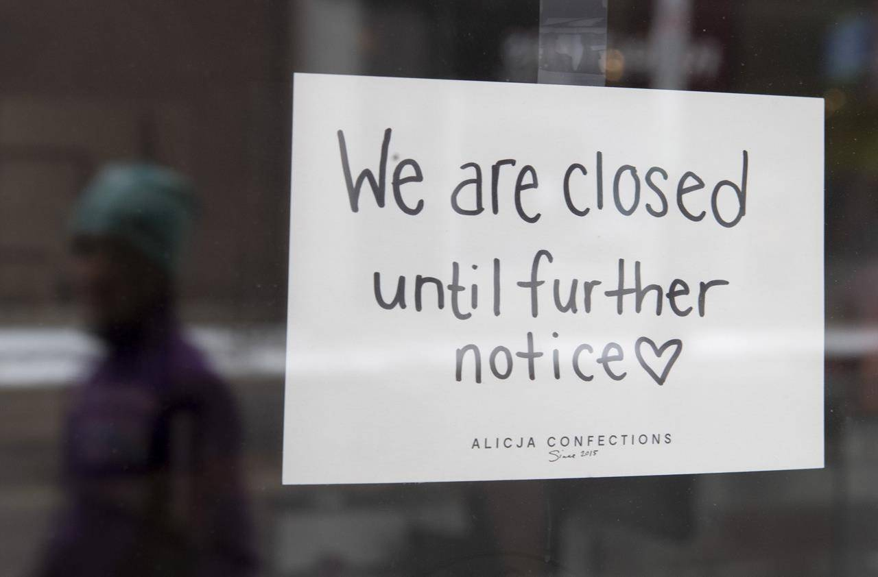 A sign on a shop window indicates the store is closed in Ottawa, Monday March 23, 2020. THE CANADIAN PRESS/Adrian Wyld