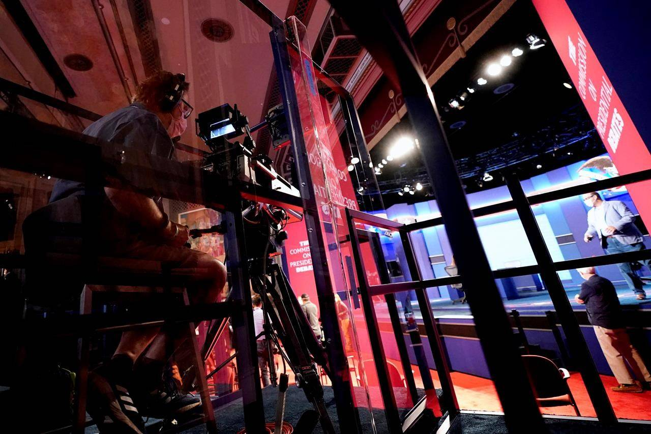A camera operator is surrounded by Plexiglas panels to protect against COVID-19 as preparations take place for the vice presidential debate at the University of Utah, Tuesday, Oct. 6, 2020, in Salt Lake City. Anyone looking for Trump-style fireworks from tonight's vice-presidential debate is likely to be disappointed. But it will still likely be one of the most watched presidential undercard debates in recent history. THE CANADIAN PRESS/AP-Julio Cortez