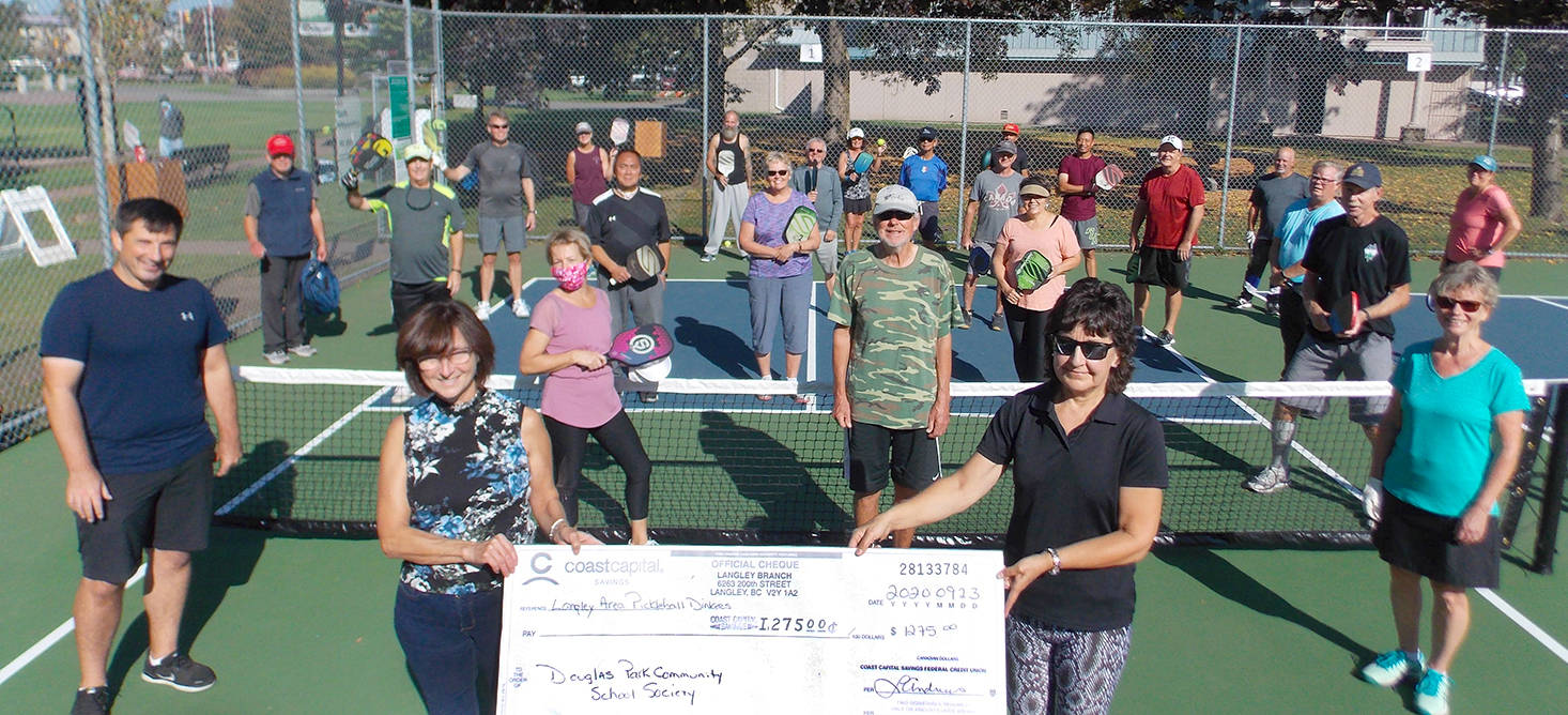 Herv Bezjak and Janet Bennett represented the Douglas Park Community School Society at the cheque presentation. Hélène Robillard, Larry Noble, Holly Tetz and Margo Barber who helped 'pass the hat' among LAPD players. Behind the net are more players in the Langley Area Pickleball Dinkers group. (LAPD/Special to the Langley Advance Times)
